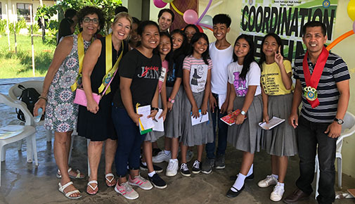 College officials pose for a photo with students and their teacher in the Philippines