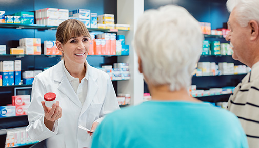 Pharmacy technician  advising senior couple on a prescription drug at a pharmacy