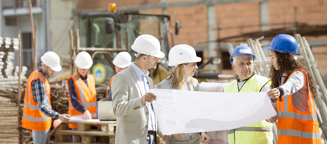 Project manager and employees reviewing blueprints at a job site